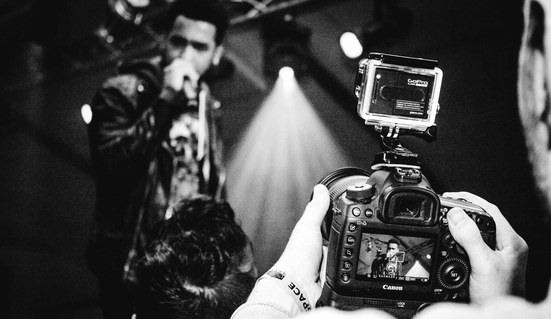 Black and white photograph of the Shoreditch Fashion Show- pictured is a camera taking a picture of a singer. Graphic design by Barefaced Studios, design agency based in Islington, North London.