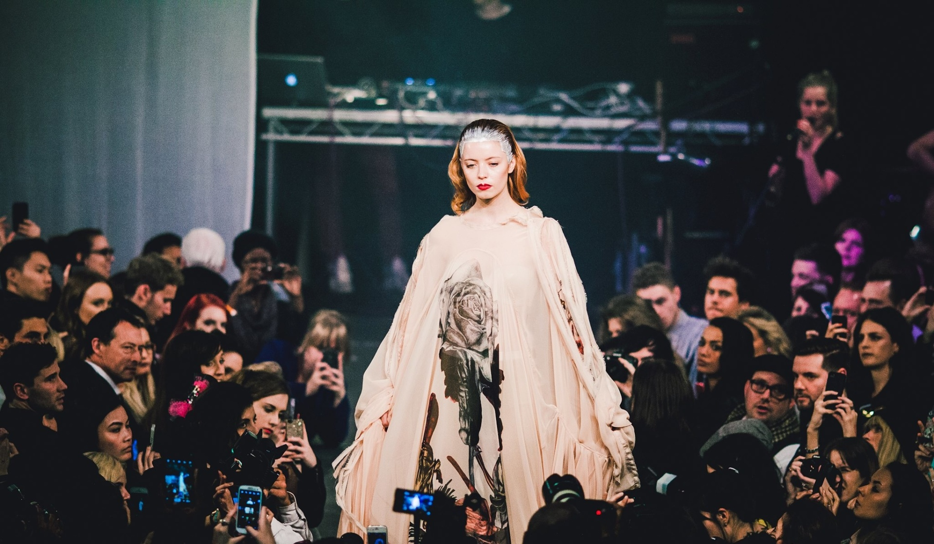 Photograph of the Shoreditch Fashion Show- pictured is a woman in white walking down a catwalk. Graphic design by Barefaced Studios, design agency based in Islington, North London.