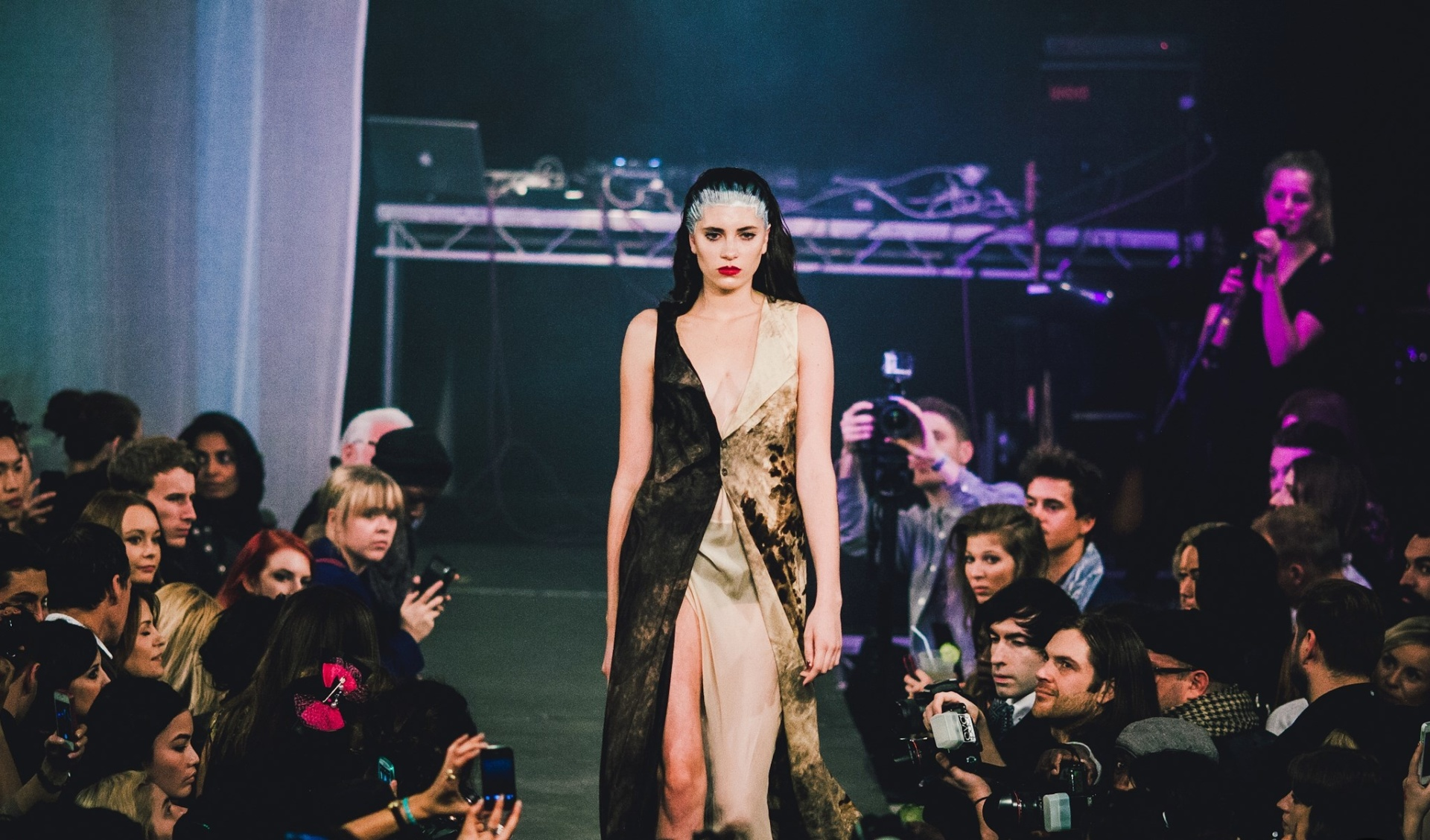 Photograph of the Shoreditch Fashion Show- pictured is a woman in a dress walking down a catwalk. Graphic design by Barefaced Studios, design agency based in Islington, North London.