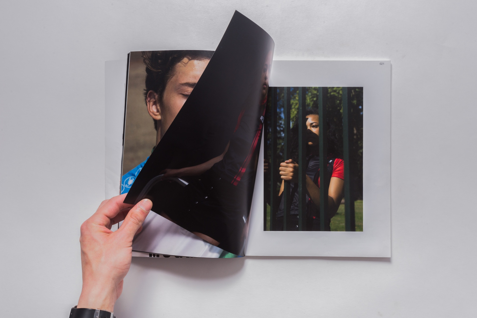 Photograph showing someone turning page of Defuze magazine, showing a women holding bars. Graphic design produced by Barefaced Studios, design agency based in Islington, North London.