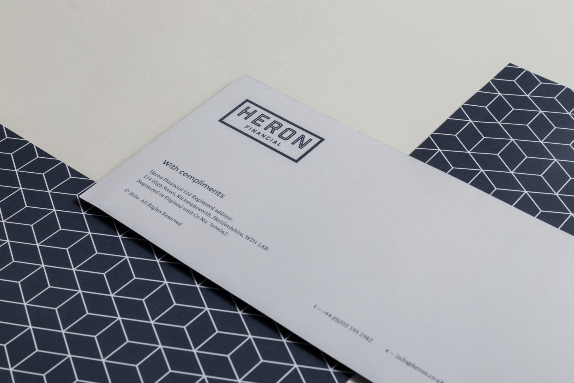 Examples of stationary design for Heron Financial, Mortgage and Insurance Brokers. Letterhead, and patterned back. Graphic design by Barefaced Studios, design agency based in Islington, North London.