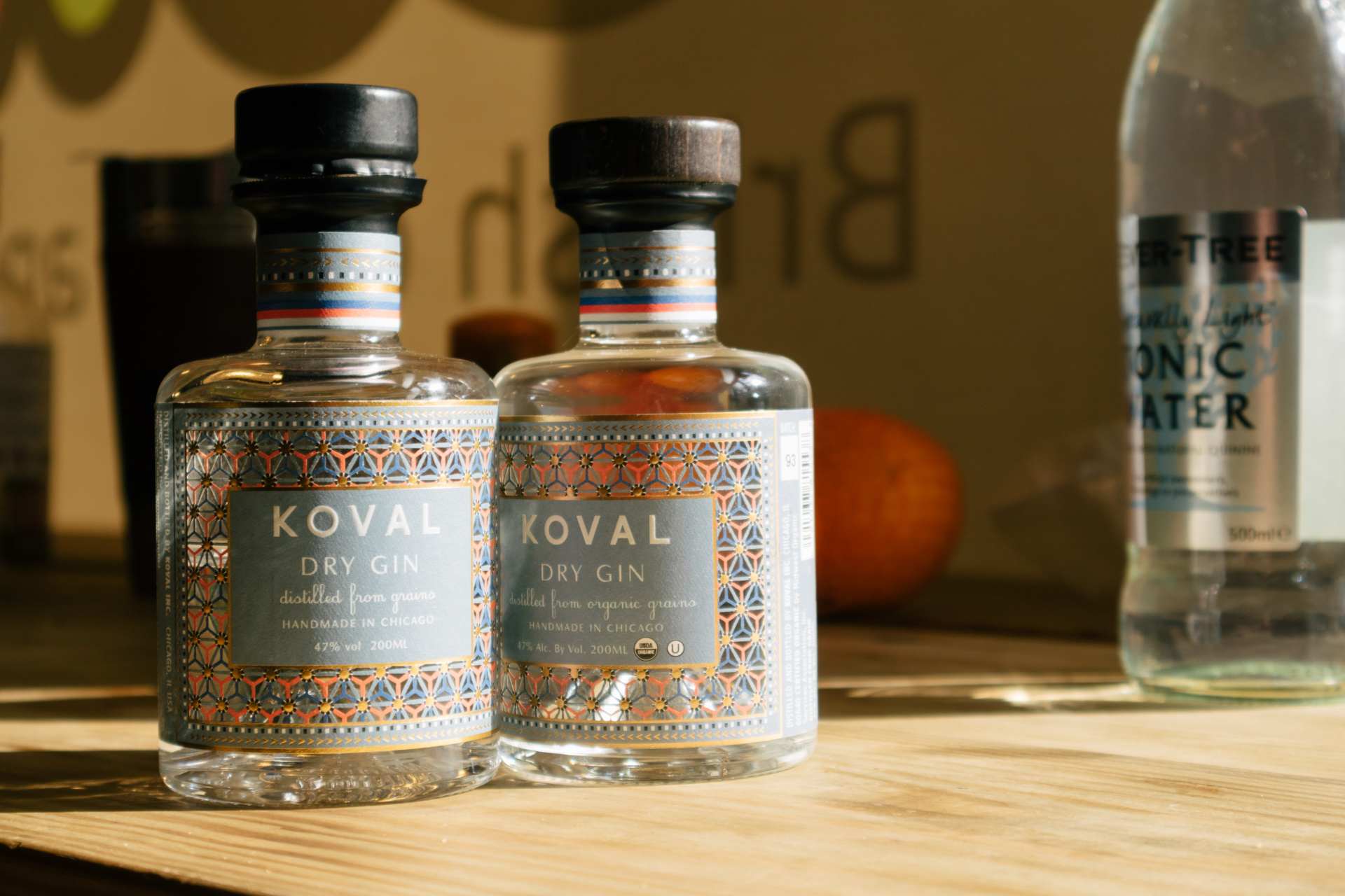 Photograph of two Koval alcohol bottles, with tonic water in the background. Produced by Barefaced Studios, design agency based in Islington, North London.