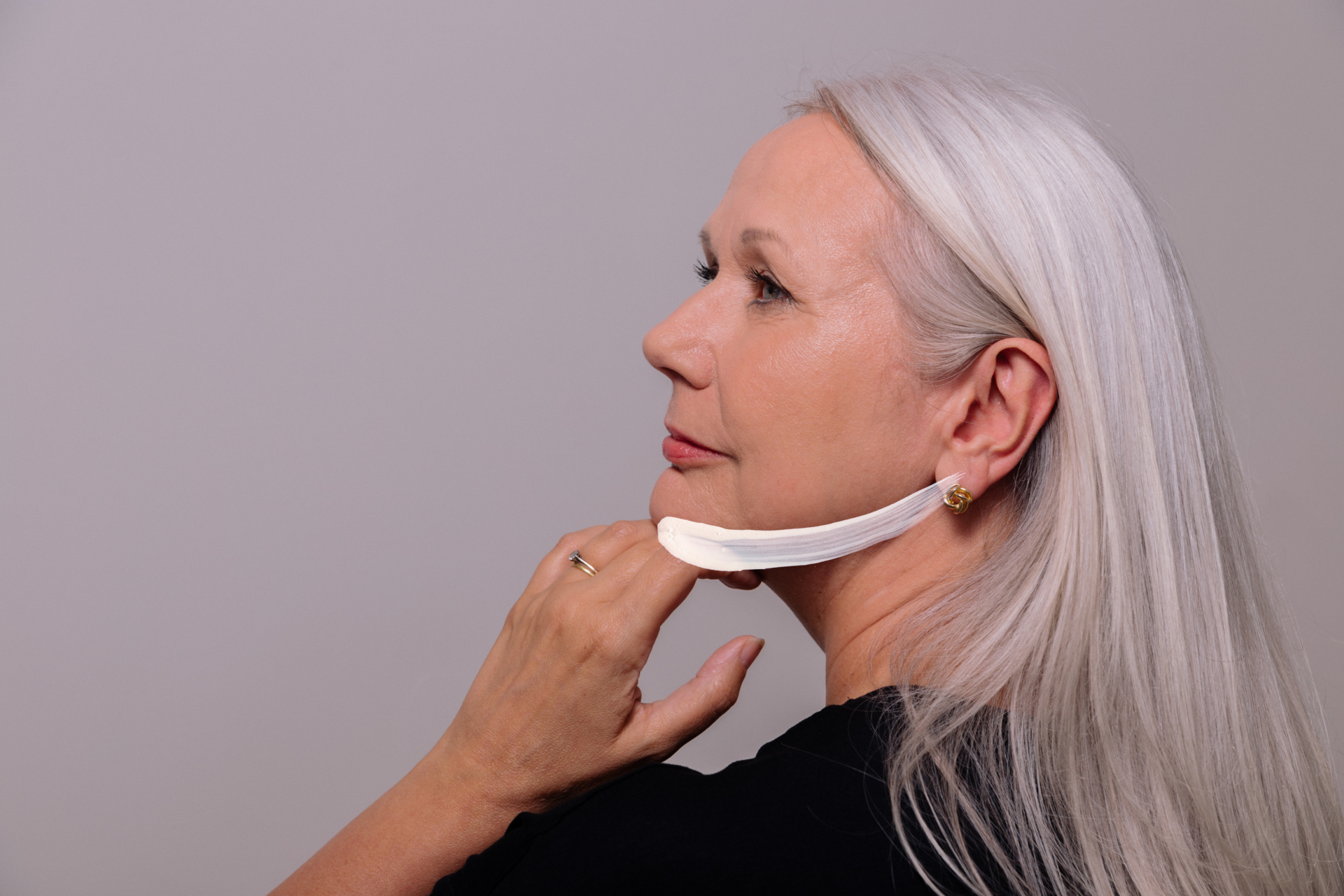 Poised woman resting hand lightly on chin with white brushstroke following chin line, designed for Harley Academy Clinic. Design by Barefaced Studios, design agency Islington.