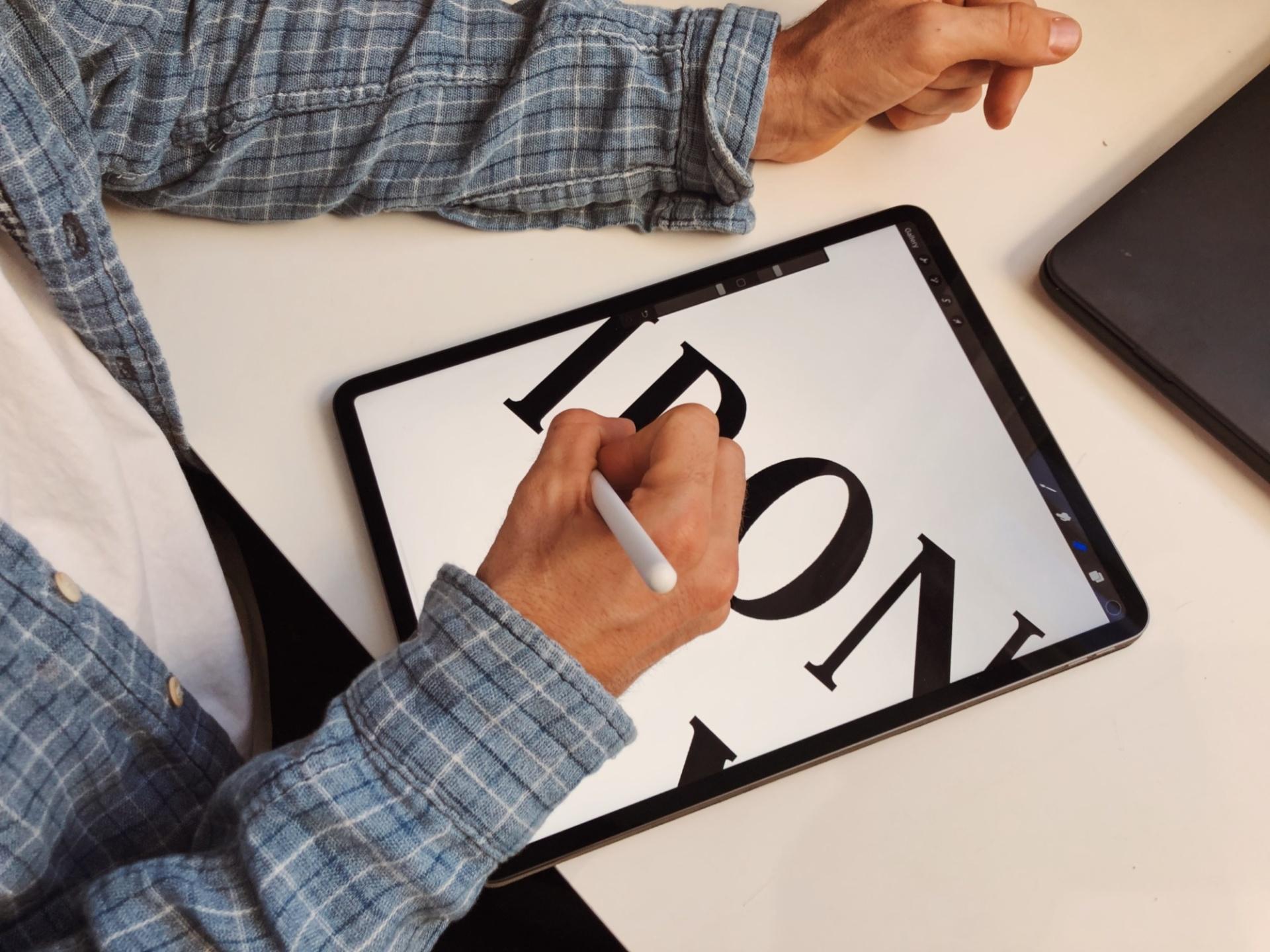 Senior Designer at Barefaced Studios sketching out the Ironworks Yard logo on an iPad.